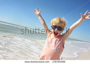 stock-photo-a-happy-young-child-is-smiling-big-and-raising-his-arms-over-his-head-in-joy-on-vacation-at-the-176785499 spring break jeune plage heureux