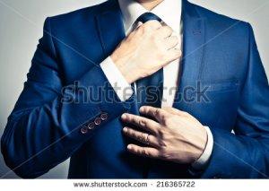stock-photo-businessman-in-blue-suit-tying-the-necktie-216365722