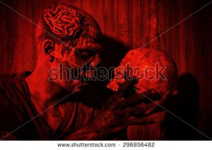 stock-photo-frightening-bloody-zombie-man-with-a-skull-in-blood-red-light-halloween-296856482 zombie