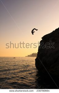 stock-photo-young-man-jumping-into-the-water-from-cliff-230790664
