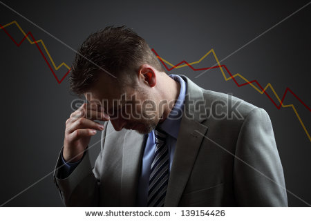 stock-photo-depressed-businessman-in-economic-crisis-with-line-graph-showing-negative-trend-139154426