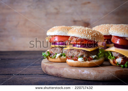 stock-photo-juicy-beef-burgers-on-wooden-background-and-the-blank-space-on-left-side-220717432