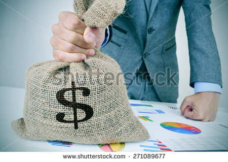 stock-photo-closeup-of-a-young-caucasian-man-in-a-grey-suit-with-a-money-bag-on-a-desk-full-of-different-charts-271089677