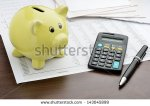 stock-photo-piggy-bank-with-calculator-and-business-reports-143045899