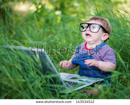 stock-photo-little-boy-playing-outdoors-with-a-laptop-143534512